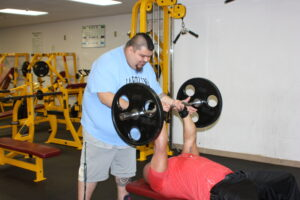 Austin Sampson (left), Cherokee Life Center fitness assistant, spots Dion Toineeta on a lift in the weightlifting room at the Cherokee Life Center on Monday, Feb. 4.  (JEAN JONES/One Feather)