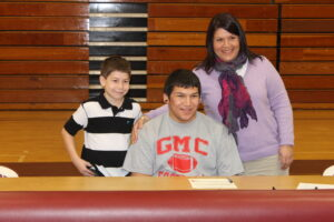 Jacob Wildcatt (sitting), shown with mother Sheila Brown (right) and brother Lucas Brown, signed to play football at Georgia Military College.
