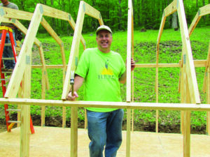 Brooks Robinson, Harrah's Cherokee general manager and senior vice president, volunteered at a home site in Big Y during the ninth annual Cherokee Day of Caring. The group of volunteers constructed a new shed and planted flowers for resident Jeremiah Long.