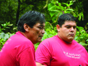 Kevin Jackson (right) listens to Tom Belt describe the significance of Judaculla Rock during a Jones-Bowman retreat.  Both are mentors in the leadership development program for college undergraduates.(CPF photo)