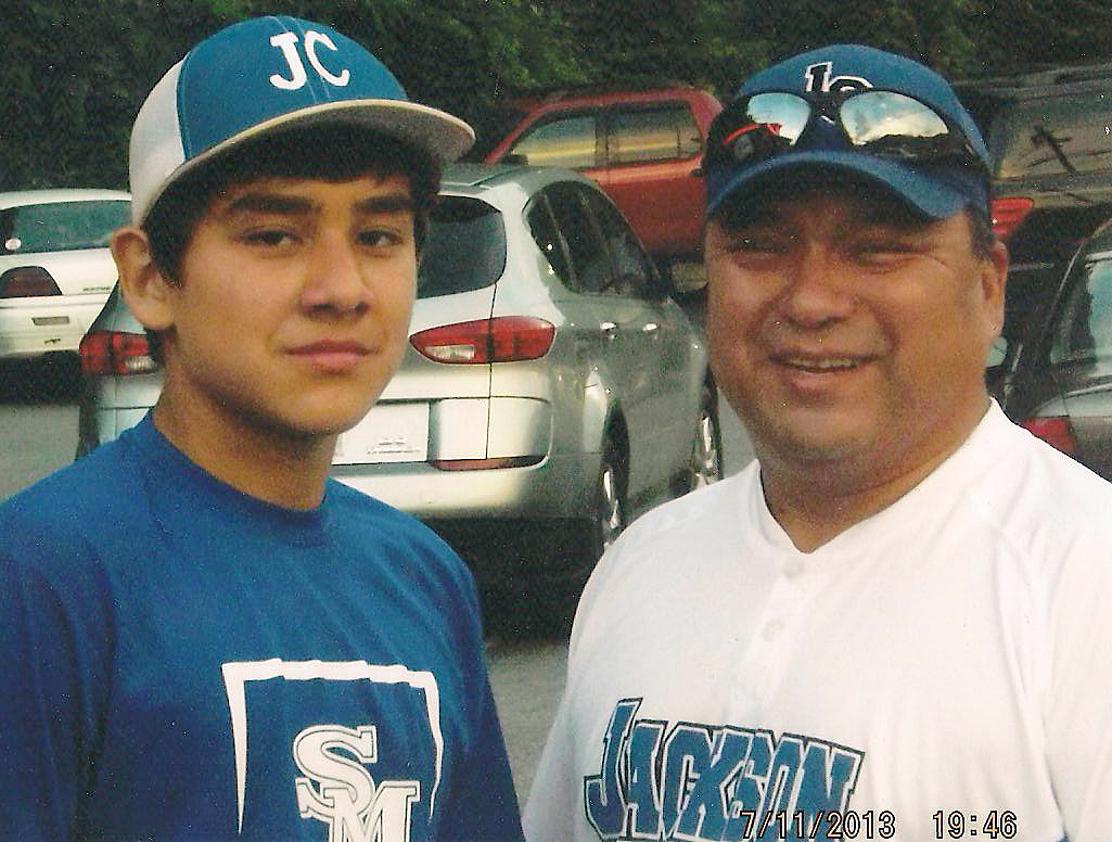 Bryce Junaluska (left), an EBCI tribal member shown with his father Carl Junaluska, is a member of the Jackson County Jr. League All-Star baseball team.  Jackson County defeated Franklin 12-1 on Wednesday, July 10 to win the North Carolina District 5 Championship.  Bryce and his team advance to the N.C. Jr. League State Championships in Boone on July 19.  Bryce, a rising freshman at Smoky Mountain High School, has been playing since the age of five.  (Photo courtesy of Carl Junaluska)