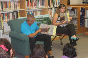 """Principal Chief Michell Hicks reads """"Let's Talk Turkey"""", the eighth book in the Cherokee Children's Book Project, to a group of children at the Qualla Boundary Public Library on Tuesday, Aug. 20. Chief Hicks signed copies of the book, and the children present received both """"Let's Talk Turkey"""" and the seventh book in the series, """"Elder Turtle"""". (SCOTT MCKIE B.P./One Feather)"""