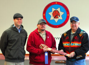 Noel Bigmeat (center) is shown here accepted the Beaded Stick Ball sticks from Boys Club President Wilbur Paul.  Paul beaded the sticks and won first place in the recent North Carolina Mountain Fair.  He donated the sticks to the Cherokee Children's Home to raffle off to help raise money for the new Children's Home facility.  Paul donated other items and sold almost 1,100 tickets himself as well. Cris Weatherford, Children's Home Manager, is shown at left.  (CBC photo)
