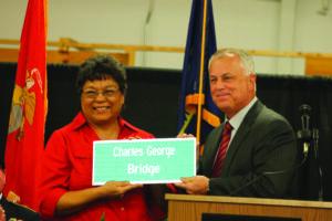 Tony Tata (right), NCDOT Secretary, presents a replica bridge sign to Patty Buchanan, niece of Charles George.