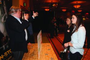 John Maney (left), Harrah's Cherokee Finance Dept., tells Cherokee High students Kendall Toineeta and Avery Mintz about cashiering.