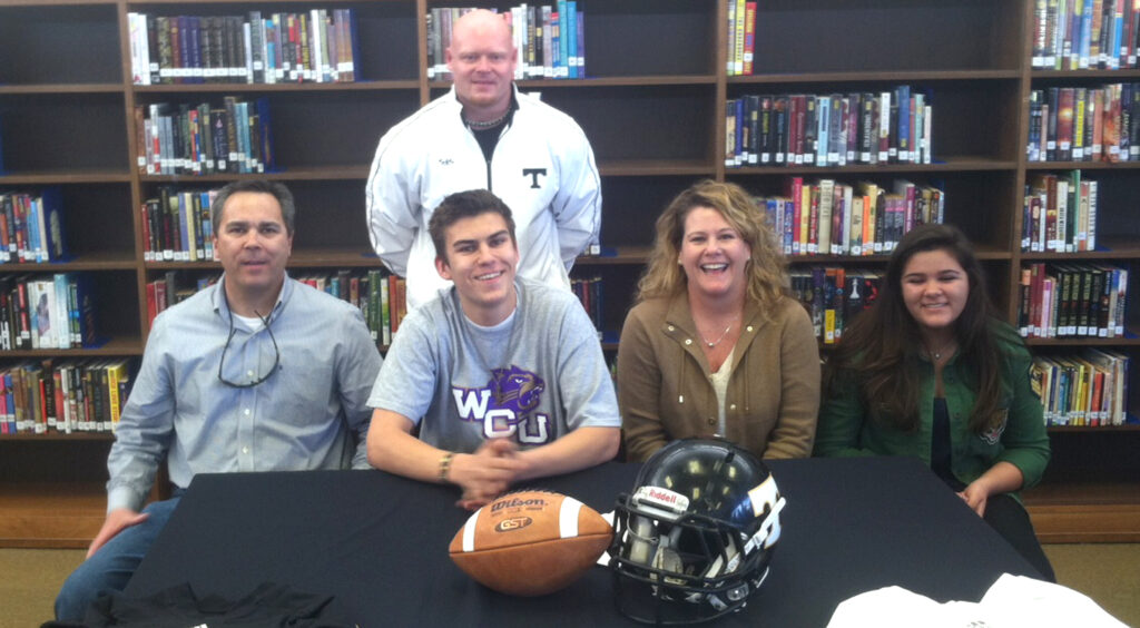 Lambert (seated 2nd from left), flanked by his family, signs a letter of intent to play football at Western Carolina University this fall.