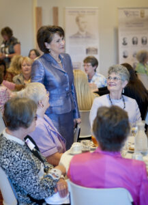 Susan Belcher (standing), wife of Western Carolina University Chancellor David O. Belcher, speaks with guests at a luncheon held in celebration of WCU's 125th anniversary. (WCU photo)