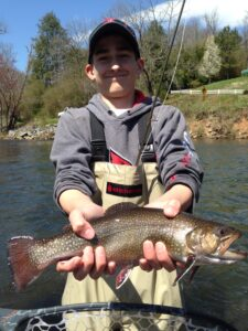 Cian Callahan, a 13-year-old from Louisville, Ky., is shown with a massive smile and his first ever fish on a fly rod, a big Brook Trout from the Tuckasegee River.  (Photo courtesy of Eugene Shuler)