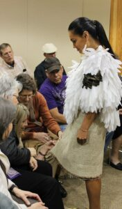 People get a closer look at a Cherokee woven skirt, a reproduction of one found in a cave in Tennessee, that is modeled by EBCI tribal member Kara Martin who will wear it as she competes at the Miss Indian World pageant later this month.