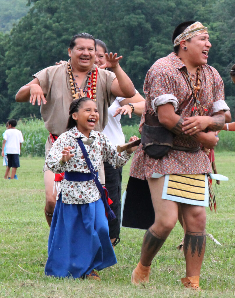 Little Miss Cherokee Tah-Tah-Yeh Swimmer is all smiles as she does the Cherokee Bear Dance at tonight's Kituwah Celebration with the Warriors of Anikituwah including Daniel Tramper (left) and her father, Micah Swimmer (right). (SCOTT MCKIE B.P./One Feather)