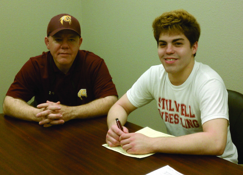 CHS graduate Levi Swearengin (right) signs a scholarship agreement on Tuesday, June 17 in Muscogee, Okla. to wrestle next season at Bacone College as his father, Anthony Swearengin, looks on.  (Photo courtesy of Swearengin family)