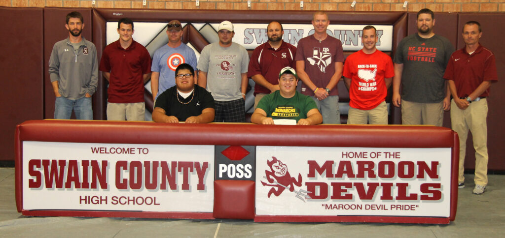 Jeremy Saunooke (seated left) and Brent Gunter (seated right) are shown at Friday's signing with their coaches.
