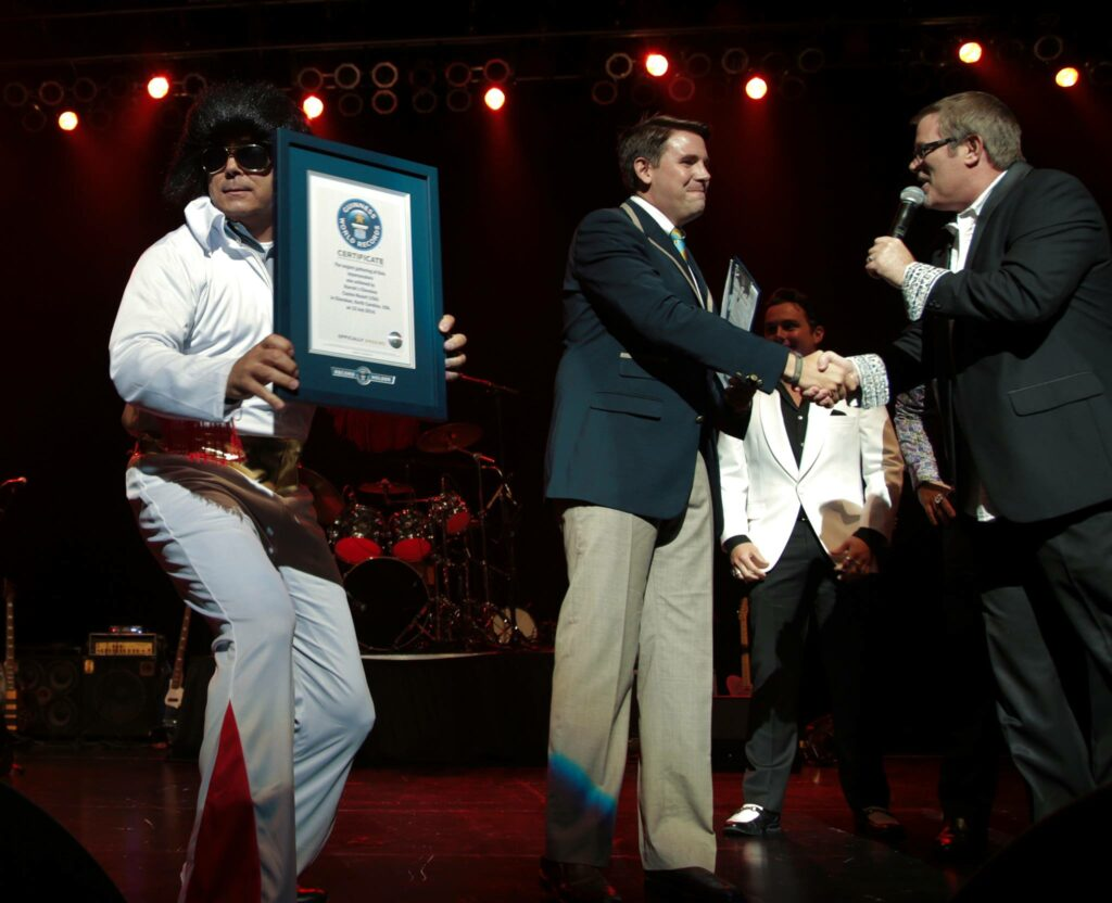 Harrah's Cherokee Valley River Casino & Hotel general manager Lumpy Lambert (center) accepts the official Guiness World Records title, while Guiness World Records adjudicator Michael Empric congratulates Kurt Brown, producer of the Ultimate Elvis Tribute Artist competition held at Harrah's Cherokee Casino Resort on Saturday, July 12.  The record was broken for the largest gathering of Elvis impersonators in the world.  A total of 895 impersonators were officially counted, breaking the 2010 record of 645.  (Harrah's Cherokee photos)