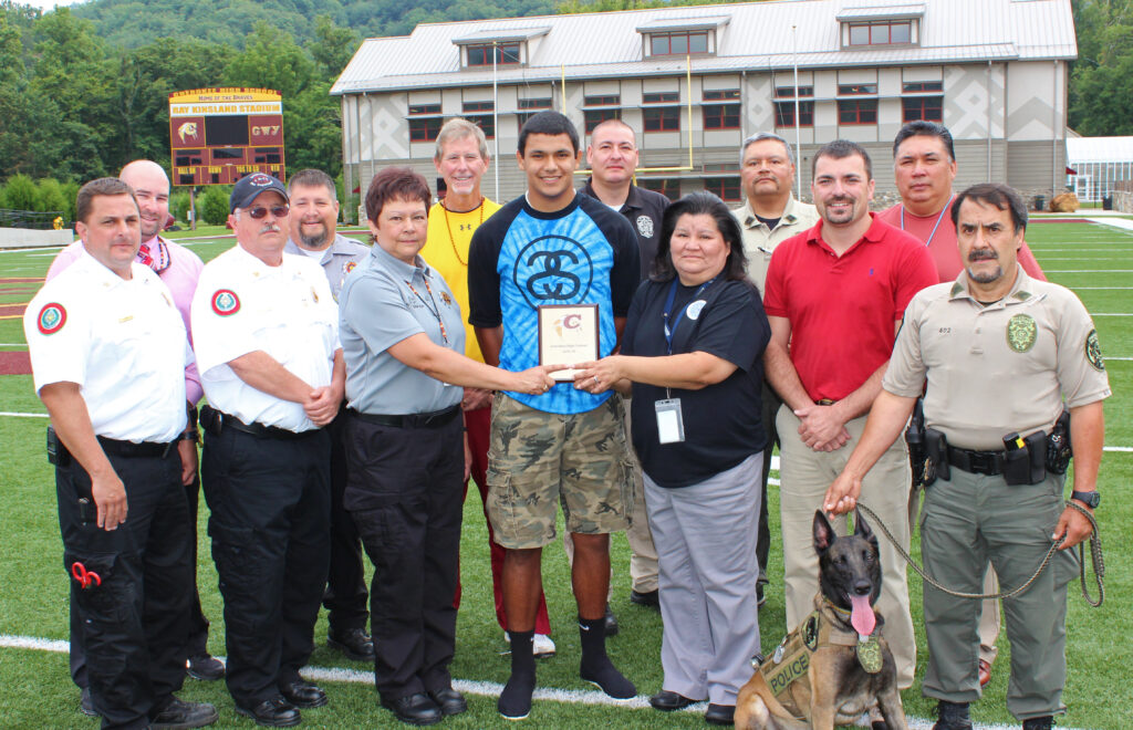 Cherokee Braves QB Brandon Buchanan (center in blue shirt) is the EBCI Emergency Management Cherokee High School Athlete of the Week for the week of Aug. 18-22.  Buchanan led the team with 285 total yards, 216 passing yards, 2 passing touchdowns, and 1 rushing touchdown in the opening game against the Tuscola Mountaineers on Friday, Aug. 22.  (AMBLE SMOKER/One Feather)