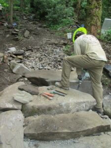 An ACE Crew Member cuts a large stone along the trail.  (NPS photo)