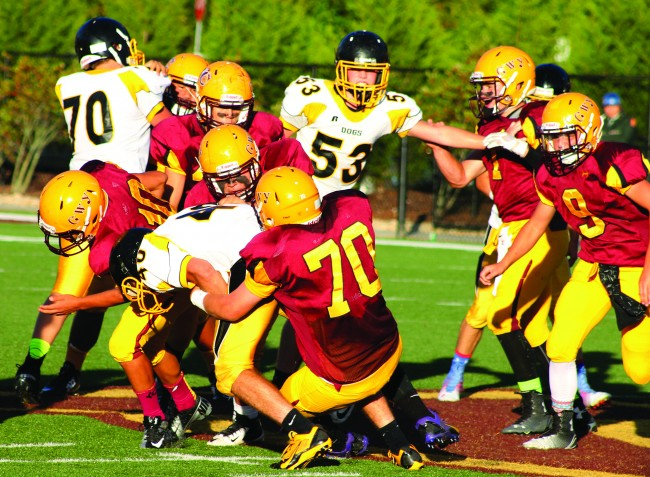 Travis Hall (#70), JV Braves defensive lineman, tackles a Murphy running back with authority.