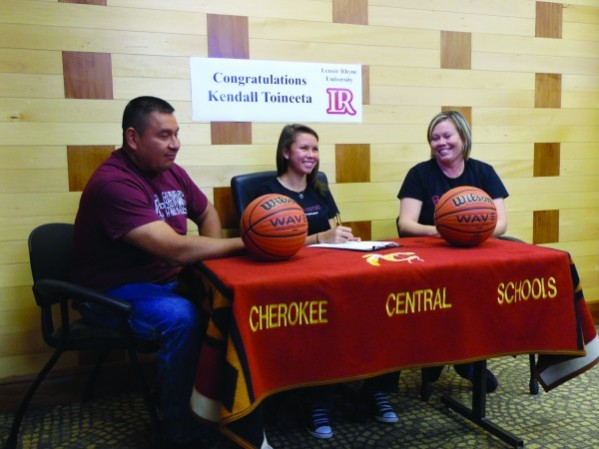 Kendall Toineeta (center), a senior at Cherokee High School, signs a letter of intent on Wednesday, Nov. 12 to play college basketball at Lenoir-Rhyne.  Last season, Toineeta averaged 19.2 pts/game for the Lady Braves and was named the Big Smoky Mountain Conference Player of the Year.  Her parents Bruce and Tonya are shown watching her sign the letter on Wednesday.  (ROBERT JUMPER/One Feather)