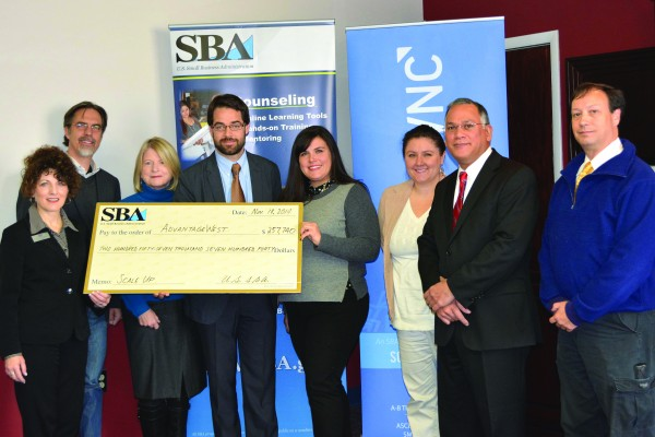 AdvantageWest executives and partners accept a ceremonial check from the U.S. Small Business Administration representing the first year's installment of a multi-year, $1.2 million contract for the ScaleUp WNC initiative, which will provide intensive growth strategy development and implementation assistance to 150 high-growth entrepreneurs in the 23-county region. Shown (left-right) are: AdvantageWest Interim Director Kathi Petersen; Steve Poland and Marilyn McDonald, from Asheville-Buncombe Technical Community College; AdvantageWest Vice President Matthew Raker; Hope Huskey, from the Sequoyah Fund; Emily Breedlove, from Small Town Ventures in Bryson City; Mike Arriola, Deputy Director of the SBA's North Carolina District Office; and 1st Vice Chair Stephen Duncan, of the AdvantageWest board of directors.  (Photo courtesy of AdvantageWest)