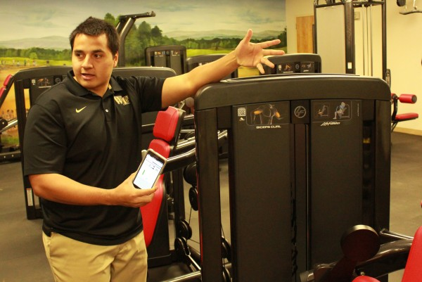 Ashford Smith, Cherokee Fitness Complex business program supervisor, demonstrates the QR Code capabilities of the new fitness equipment where users can get information and tutorials on how to properly use the machines.   (AMBLE SMOKER/One Feather photos)