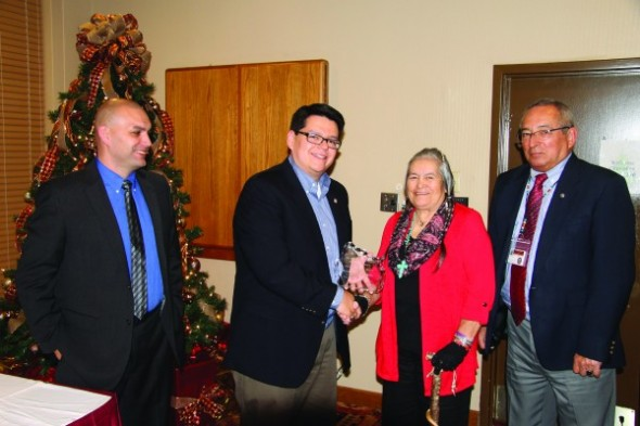 Wren Peterson (2nd from right) and Butch Sanders (right), two of the children of Katherine Blythe Sanders, accept the 2014 Frell Owl Award on behalf of their mother, from Skooter McCoy (left), Cherokee Boys Club executive director, and Cory Blankenship, Cherokee Boys Club Board of Directors president, during a ceremony on Wednesday, Dec. 17.  (SCOTT MCKIE B.P./One Feather)