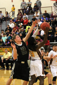 J.J. Benjamin (#23), Braves forward, goes inside and around Hayesville's Braxton Cox (#20) for a layup in the first half of Friday's home game.  Benjamin had 11 points on the night.