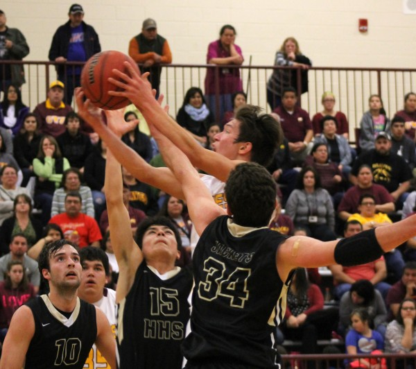 Dustin Johnson (center), Braves senior point guard, threads the needle as he goes for a shot between Hayesville's Hunter Reaux (#15) and Zach Cottrell (#34) during a home game on Friday, Jan. 2.  Johnson led Cherokee with 30 points as the Braves stayed undefeated and took control of first place in the Big Smoky Mountain Conference with a 65-53 win.  (SCOTT MCKIE B.P./One Feather)