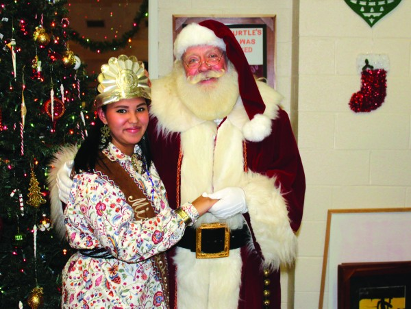 Miss Cherokee Taylor Wilnoty visits with Santa Claus at the Tsali Care Christmas Party.  (Photo courtesy of Taylor Wilnoty)