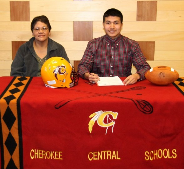 With his mother, Susan Lossiah, looking on, Channing Lossiah, Cherokee Braves linebacker and wide receiver, signs a letter of intent on Friday, Feb. 6 to play college football for Lenoir-Rhyne University.   (SCOTT MCKIE B.P./One Feather)