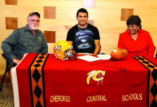 With his parents Omer Buchanan (left) and Patty Buchahan (right) watching, Brandon Buchanan signs a letter of intent on Wednesday, Feb. 4, National Signing Day, to play college football at Lenior-Rhyne University.  (SCOTT MCKIE B.P./One Feather)