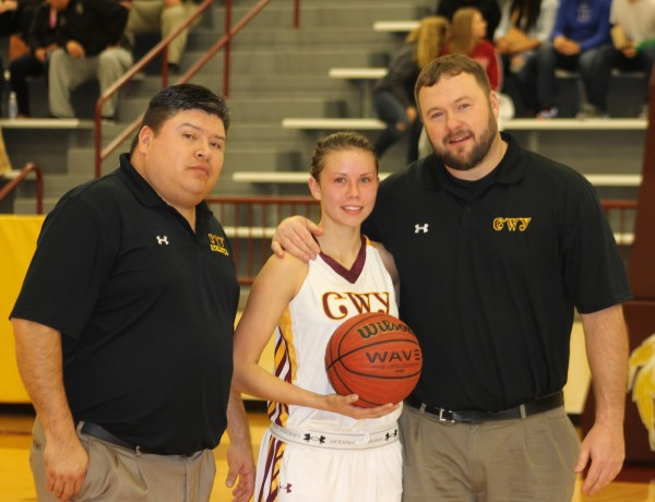 Kendall Toineeta (center), Lady Braves senior point guard, scored her 2,000th career point during a home game on Saturday, Feb. 7.  She is shown with Lady Braves assistant coach Ben Stamper (left) and Lady Braves head coach Chris Mintz as she was honored during halftime.  (SCOTT MCKIE B.P./One Feather)