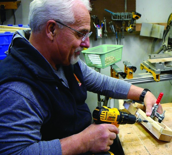 """Great Smoky Mountains National Park seasonal ranger Mike Meldrum builds a """"dancing bear"""" old-fashioned wooden toy in his workshop.  (GSMA photos)"""