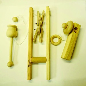Mike Meldrum's old-fashioned wooden toy set includes, from left, a ball and cup, a dancing bear, and a spinning top.