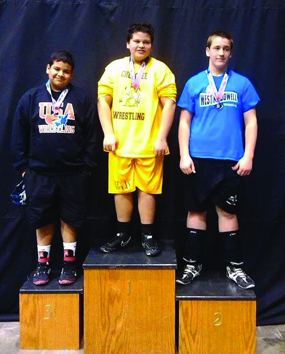 Rider Sneed (center), a member of the Cherokee Middle School wrestling team, took first place in the 7th grade 220lb division at the Middle School state championship meet in Winston-Salem on Feb. 6-7.   (Photo courtesy of Anthony Swearengin)
