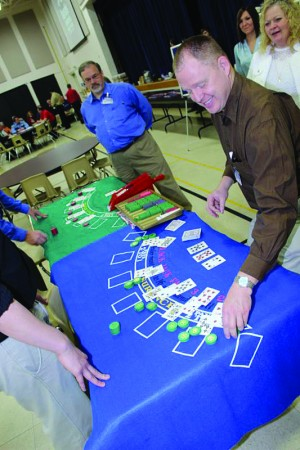 Table Games Dealer Brian Simmons demonstrates black jack at the Harrah's Cherokee Valley River Casino & Hotel job fair at Tri-County Community College. The job fair drew more than 500 people, and more than 200 were offered positions. (Harrah's Cherokee photo)