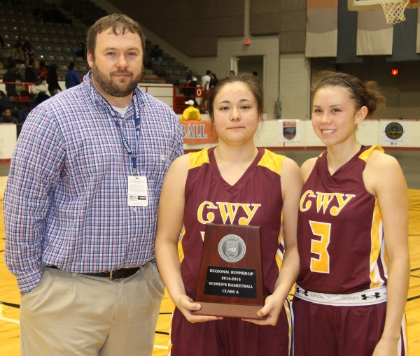 Lady Braves head coach Chris Mintz and team captains Peri Wildcatt and Kendall Toineeta hold the plaque the team received on Saturday, March 7 for being the 1A West Regional Runner-Up.   (SCOTT MCKIE B.P./One Feather photos)