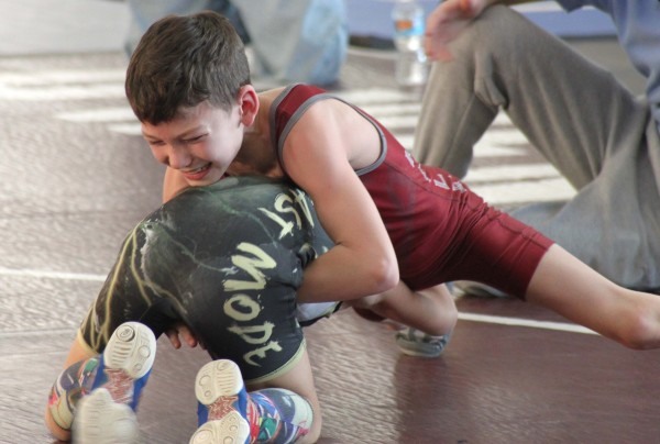 Kale Stephenson, a member of the Cherokee Youth Wrestling team, works hard during a match at the Headlock on Hunger tournament at UNC – Asheville on Saturday, March 7.  He took second place Intermediate 50-55 division.  (Photo by Shannan Sneed)