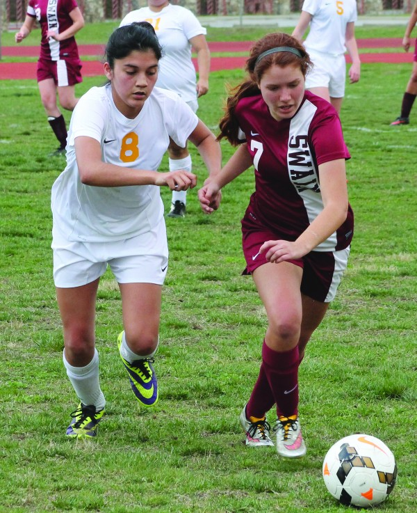 Cherokee's Sidnie Yanez (#8) and Swain's Storm Ledford (#7), both EBCI tribal members, sprint for the ball during a home match on Monday, March 23.  Ledford scored four goals as Swain was victorious over the Lady Braves 5-1.  (SCOTT MCKIE B.P./One Feather)
