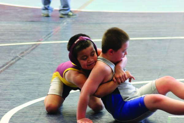 Talon Crowe (back), Cherokee Youth Wrestling team, works hard against Colten McFalls, Jackson County Youth Wrestling, during a Bantam bout at the Jet Rumble at Enka High School on Saturday, March 21.  (Photo by Alica Wildcatt)