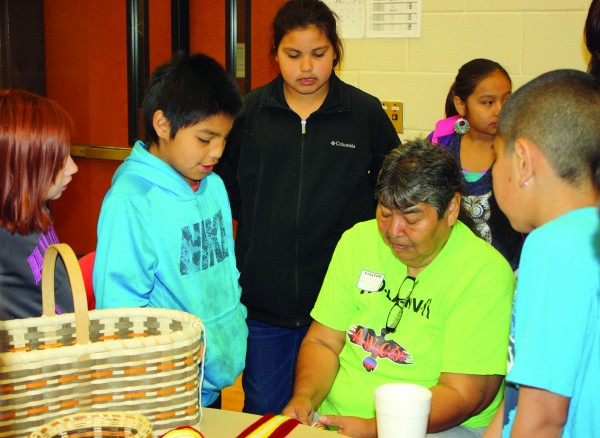 Ruth Lossiah (seated center) demonstrates the art of fingerweaving to Ms. Hall's fourth grade class at Cherokee Elementary School.   (CCS photos)