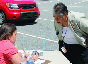 Sky Kanott (seated), Cherokee Youth Council manager, registers Evelyn Locust at Wednesday's event.