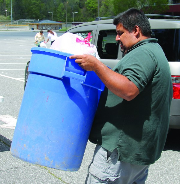 T. Trejo, Tribal Recycling Program manager, unloads a barrel of recycled products brought by Mary Long, of the Wolfetown Community, to the Gadugi Earth Day event at the Acquoni Expo Center on Wednesday, April 22.  (SCOTT MCKIE B.P./One Feather photos)