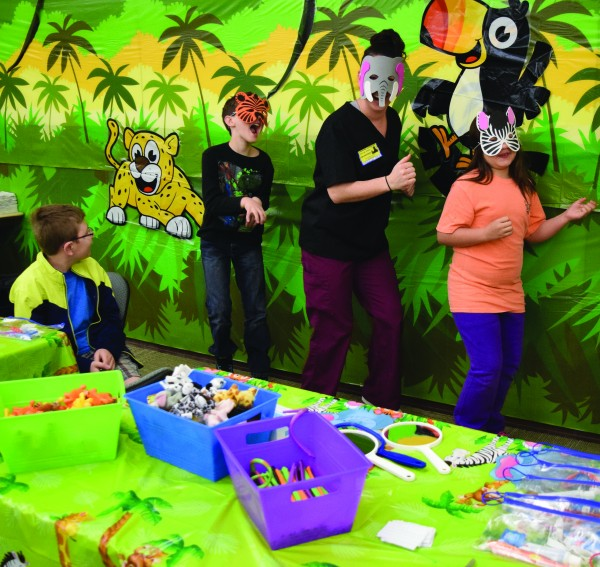 """Thomas Armachain (seated) watches Christian Hensley; Crystal Shaw, a dental student from the University of New Haven Connecticut; and Kaiden Lambert prowl through the """"jungle"""" at the recent """"Sealant Safari"""" at Cherokee Elementary School.  (PHHS photo)"""