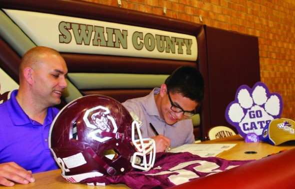 Spencer McCoy (right), Swain County football stand-out, signs a letter of intent on Monday, April 6 to play at Western Carolina University this fall as his father, Spencer McCoy, looks on.  (AMBLE SMOKER/One Feather photos)