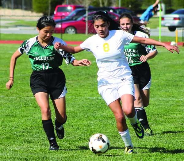 Cherokee's Sidnie Yanez (#8) dribbles the ball past two Tallulah Falls defenders including Riko Miyazaki (#12) and Laura Ramos (#14) in a home game on Tuesday, April 21.  (SCOTT MCKIE B.P./One Feather)