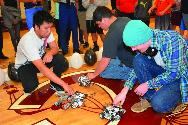 Cherokee's Taylor Wachacha (left), Hiwassee Dam's Keith Hackler (center) and Pisgah's Nick Abbott press the 'start' button their teams' respective robots during a recent robotics competition in Cherokee. (SCC photos)