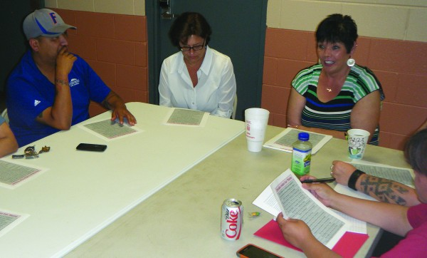 Chris Watty, Janet Owle, and Frieda Huskey, along with other members of the Fair Committee, review the theme submissions being considered for this year.  (ROBERT JUMPER/One Feather)