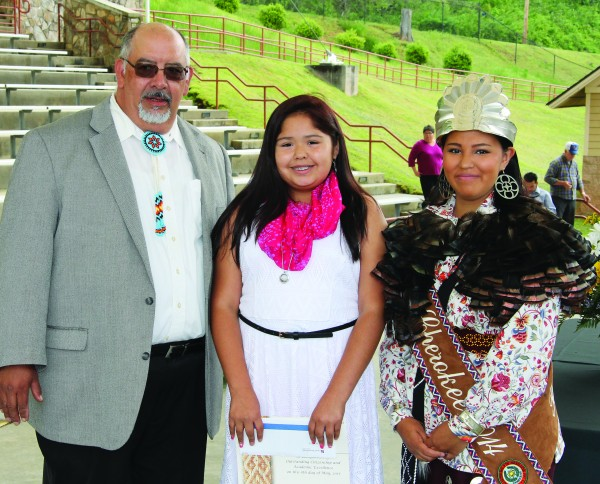 Praire Toineeta (center) was named Best All-Around at New Kituwah Academy during the annual Tribal Council Awards Day held at the Cherokee Indian Fairgrounds on Friday, May 8.  She was presented her award by Big Cove Rep. Perry Shell (left) and Miss Cherokee 2014 Taylor Wilnoty.  (SCOTT MCKIE B.P./One Feather)