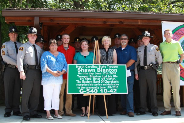 Friends, family and colleagues pose in front of a sign that will be placed at #24 bridge in downtown Cherokee as it was dedicated to the late Trooper David Shawn Blanton (G540) on Wednesday, June 17.   (AMBLE SMOKER/One Feather photos)