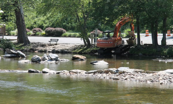 Tribal Construction crews have been placing large boulders into the Oconaluftee River this past week as part of the Island Park Restoration Project.  (SCOTT MCKIE B.P./One Feather)