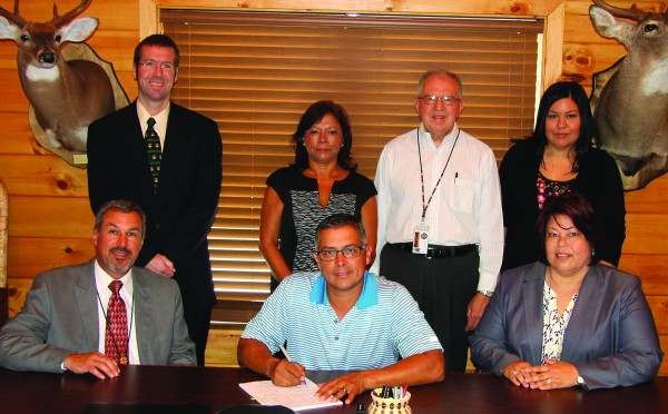 """On Monday, June 15, Principal Chief Michell Hicks (seated center) signs Ord. No. 526 into law which outlines provisions for the Eastern Band of Cherokee Indians to enact the Special Domestic Violence Criminal Jurisdiction outlined in the VAWA Reauthorization of 2013.  Shown (left-right) seated – Cherokee Chief Justice Bill Boyum, Chief Hicks, Tribal Council Chairperson Terri Henry; standing – Tribal Prosecutor Jason Smith; Iva Keys, EBCI Domestic Violence Program manager; J.T. Garrett, EBCI Human Services director; and Billie Jo Rich, an EBCI tribal member who stars in an American Indian play about domestic violence entitled """"Sliver of a Full Moon"""".  (SCOTT MCKIE B.P./One Feather)"""